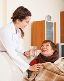 caring nurse giving glass to   woman