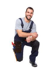 Portrait of smiling worker kneeling with hand doing ok gesture