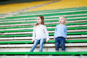 Two little sisters sitting on a stadium seats