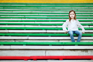 Cute girl sitting on a stadium seat