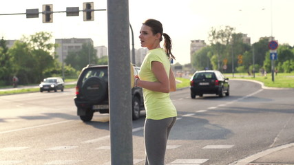 Young woman jogging through zebra crossing