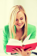 smiling young woman reading book at school