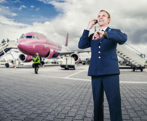 Aircraft pilot talking by phone on airport runway before flight