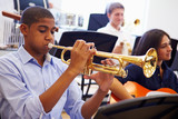 Fototapety Male Pupil Playing Trumpet In High School Orchestra