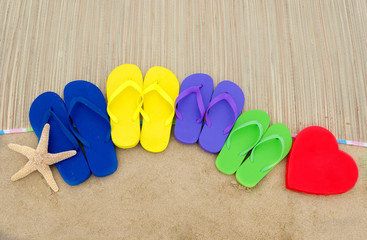 Color flip flops and heart on sandy beach