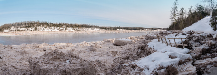 Panorama of forest river covered with snow and ice