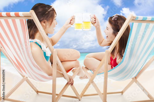 two sunshine girl holding beer cheers  on a beach chair