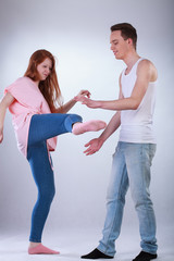 Teenage girl kicking a boy