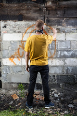 Male hooligan painting graffiti