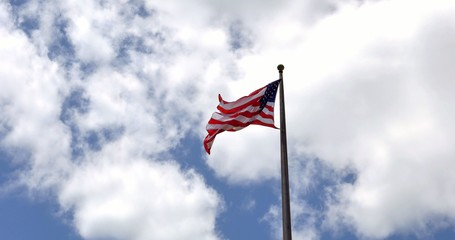 4K American flag - star and stripes floating over a blue sky