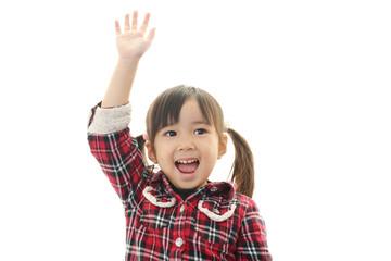 手を挙げて返事している笑顔の園児