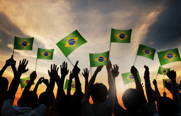 Silhouettes of People Holding the Flag of Brazil