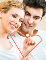 Young amorous couple with heart symbol