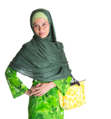 Muslim woman in green dress, hijab with yellow handbag