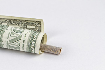 Cigarette wrapped in a 1 dollar bill