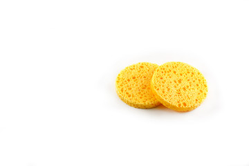 A round yellow natural facial sponge isolated on white