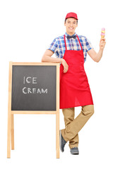 Ice cream vendor standing by a blackboard