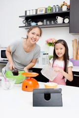 Adorable Asian family baking together in the kitchen