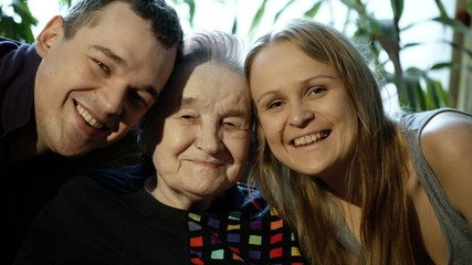 Young man and woman kissing grandmother on cheeks