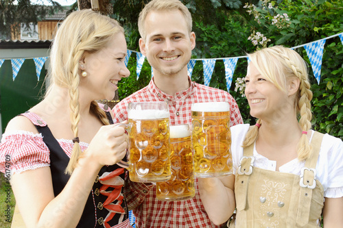 Gäste im Biergarten feiern Oktoberfest - 66174709