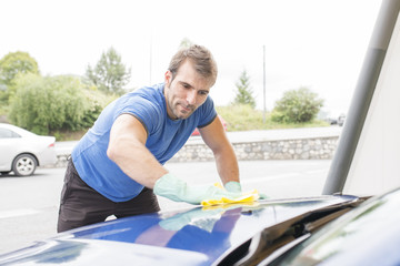 Man cleaning car with sponge.