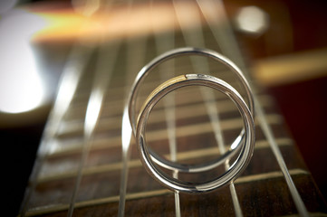 Wedding rings on the cords of the guitar
