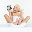 Happy woman with alarm clock awakes