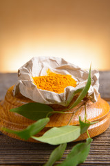 Tumeric powwder spice on wooden board with fresh leaves