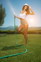 Beautiful young woman having fun in summer garden with garden ho