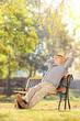Elderly gentleman sitting on a bench in park