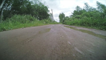 Dirty rural dirt road with puddles after rain