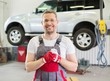Cheerful serviceman wearing overall in car workshop
