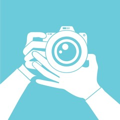 hand holding camera blue background