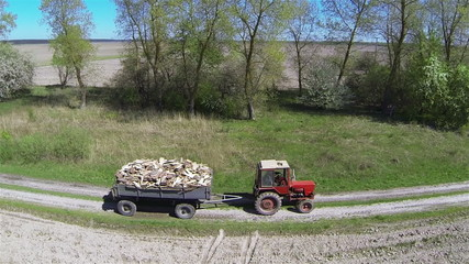 Rural tractor with  trailer of firewood. Aerial view