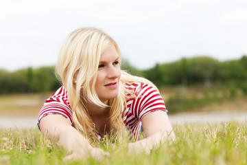Junge blonde Frau im Gras liegend
