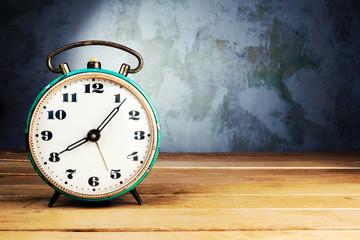 Retro alarm clock on wooden table