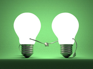 Glowing light bulbs handshaking on green
