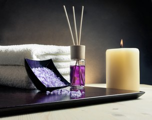 Spa massage with towel stacked, perfume diffuser and sea salt