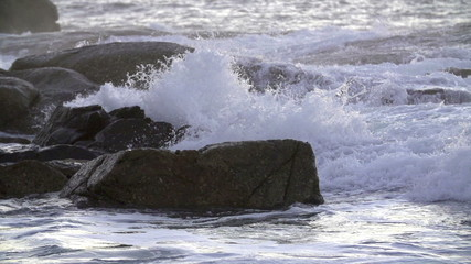 Waves splashing over rocks in slow motion