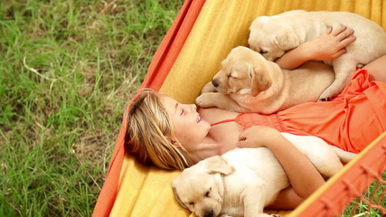 girl swinging in hammock with puppies