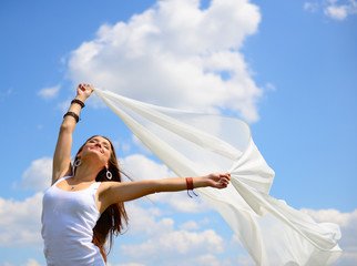 Happy young woman holding white scarf with opened arms expressin