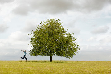 Frau läuft zum Baum