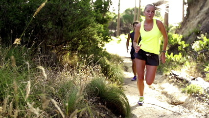 Couple jogging on forrest path in slow motion