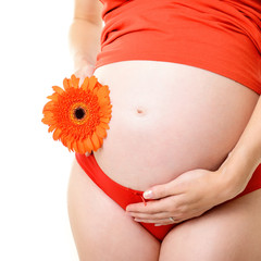 unrecognizable pregnant woman in red with deep orange flower, is