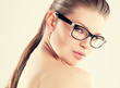 Fashion pretty girl in spectacles posing in studio