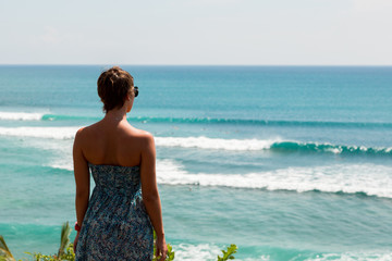 woman standing on the edge of the rock. surfing