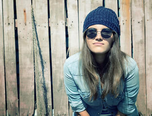 beautiful cool girl in hat and sunglasses against grunge wooden