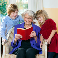 Grandmother Reading Book to Grand Children.