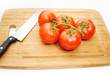 Tomatoes on a Cuting Board with a Knife