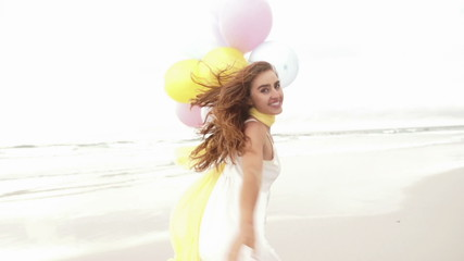 Girl with colorful balloons on beach